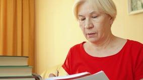 Mulher superior que aprende a gramática da língua estrangeira Respostas superiores da escrita do estudante fêmea no livro de text vídeos de arquivo