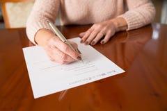 A mulher superior que assina por último e testamento em casa fotografia de stock