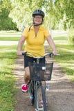 Mulher superior que bicycling em um parque na tarde ensolarada foto de stock royalty free