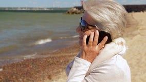 Mulher superior que chama o smartphone na praia do verão filme