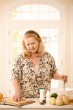 Mulher que verifica a receita na cozinha imagens de stock royalty free