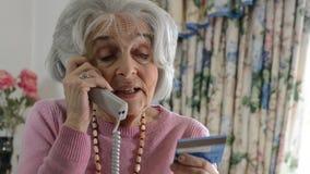 Mulher superior que dá detalhes do cartão de crédito no telefone filme