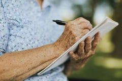 Mulher superior que escreve para baixo suas memórias em um caderno imagens de stock