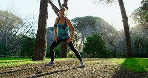 Mulher superior que exercita no parque 4k video estoque
