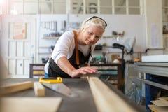 Mulher superior que faz a carpintaria em uma oficina Imagens de Stock