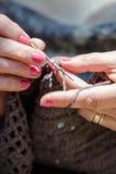 Mulher superior que faz crochê uma cobertura marrom que relaxa no jardim Fotografia de Stock