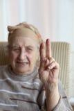 Mulher superior que faz o sinal da vitória Foto de Stock Royalty Free