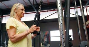 A mulher superior que faz o tríceps exercita no estúdio 4k da aptidão filme