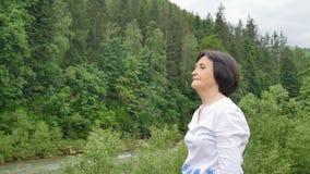 Mulher superior que faz um exercício de esticão para a parte externa dos úmeros sobre a paisagem da floresta e das montanhas video estoque