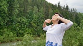 Mulher superior que faz um exercício de esticão para a parte externa dos úmeros sobre a paisagem da floresta e das montanhas vídeos de arquivo