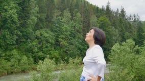 Mulher superior que faz um exercício de esticão para a parte externa dos úmeros sobre a paisagem da floresta e das montanhas filme