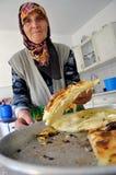 Mulher superior que faz uma torta tradicional em casa em sua cozinha imagens de stock