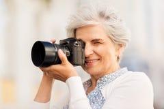 Mulher superior que fotografa pela câmara digital fotos de stock royalty free