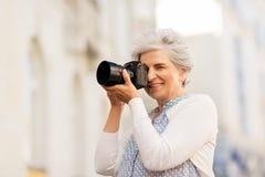 Mulher superior que fotografa pela câmara digital imagens de stock