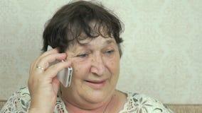 Mulher superior que guarda a conversa do smartphone ao doutor vídeos de arquivo