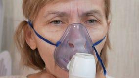 Mulher superior que guarda uma máscara de um inalador em casa Trata a inflamação das vias aéreas através do nebulizer Impedindo a video estoque