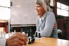 Mulher superior que joga a xadrez em uma sala de aula imagens de stock