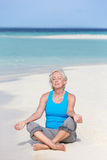 Mulher superior que Meditating na praia bonita Imagens de Stock Royalty Free