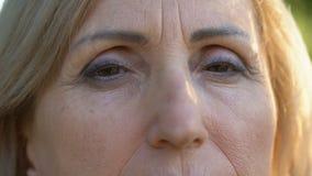 Mulher superior que olha na câmera, na idade e nos enrugamentos, close-up dos olhos fêmeas vídeos de arquivo