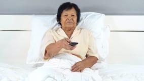 Mulher superior que olha o filme assustado com controlo a distância da tevê na cama