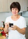 Mulher superior que olha o telefone foto de stock
