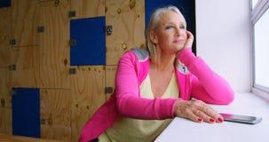 Mulher superior que olha para fora através da janela no estúdio 4k da aptidão vídeos de arquivo