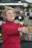 Mulher superior que pesa o abacaxi Imagem de Stock Royalty Free