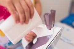 Mulher superior que reenche o ferro com água destilled Fotografia de Stock