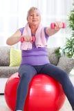 Mulher superior que sentam-se na bola do gym, e exercício com pesos em h Foto de Stock Royalty Free