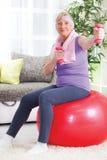 Mulher superior que sentam-se na bola do gym, e exercício com pesos em h Imagem de Stock Royalty Free