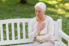 Mulher superior que sente doente no parque do verão foto de stock