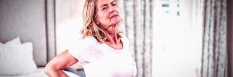 Mulher superior que tem a dor nas costas no quarto imagem de stock royalty free