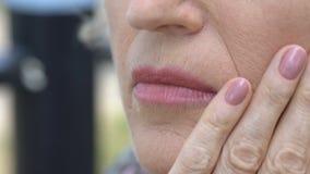 Mulher superior que toca em sua cara enrugada, processo do envelhecimento da pele, desejo ser novo filme