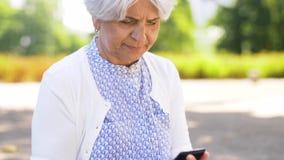 Mulher superior que toma o smartphone fora do saco no parque vídeos de arquivo
