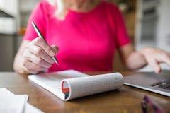 Mulher superior que trabalha em casa tomando notas Imagem de Stock Royalty Free