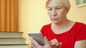 Mulher superior que usa a aplicação para aprender línguas estrangeiras no smartphone, fazendo o treinamento em-app vídeos de arquivo