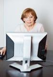 Mulher superior que usa o computador na classe imagens de stock