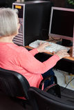 Mulher superior que usa o computador na mesa na sala de aula foto de stock