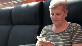 Mulher superior que usa o smartphone moderno e o sorriso filme