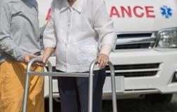 Mulher superior que usa um caminhante com cuidador Fotografia de Stock Royalty Free