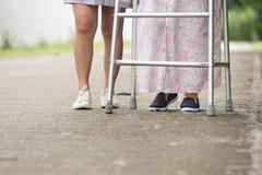 Mulher superior que usa um caminhante com cuidador Fotos de Stock Royalty Free