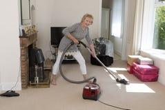 Mulher superior que usa um vácuo durante uma sessão dos trabalhos domésticos Foto de Stock Royalty Free