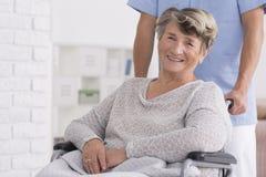 Mulher superior sorrida com seu cuidador fotos de stock royalty free