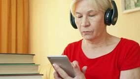 A mulher superior usa a aplicação para o treinamento de habilidades de escuta, aprendendo a língua estrangeira no smartphone video estoque