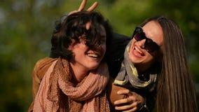 A mulher surpreendente com cabelo encaracolado curto está levando seu amigo fêmea nos óculos de sol nos ombros Dois atrativos vídeos de arquivo