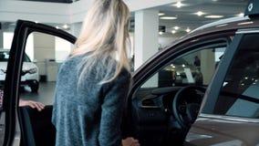 Mulher surpreendente do homem com o carro novo na sala da mostra video estoque