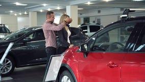 Mulher surpreendente do homem com o carro novo na sala da mostra fotos de stock