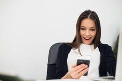 Mulher surpreendente feliz que olha no telefone celular e que lê a mensagem com boca aberta Foto de Stock Royalty Free