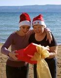 A mulher surpreendida abre um presente do Natal Fotografia de Stock
