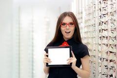 Mulher surpreendida com a tabuleta do PC na loja ótica médica Fotografia de Stock Royalty Free